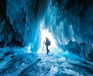un montaero se detiene en una cueva de hielo en el lago baikal
